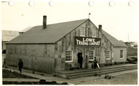 "Exterior of small warehouse with ""Lowe Trading Company"" sign above door"