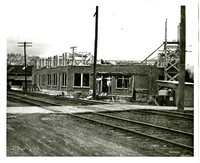 Construction of the brick headquarters of Pacific American Fisheries at 4th and Harris streets, with railroad running adjacent, south Bellingham, WA