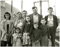 """The Satko family of 9 stand somberly on dock with their """"Ark of Juneau"""" boat in background"""