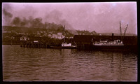 """Negative of wooden steamship """"Pavlof"""" and tugboat in Bellingham Bay at Fairhaven (Bellingham), Washington, with Pacific American Fisheries facilities and dock on shore behind, South Hill neighborhood in background"""