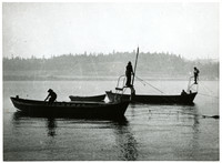 Two canoes rigged for reefnetting, each with two men, fish the waters off Gooseberry Point