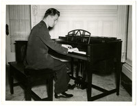 Gunnar Anderson at age thirty-one, dressed formally, playing a piano, seated with his side to the camera