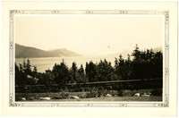 Roadside guardrail with trees beyond, bay of water and islands in distance