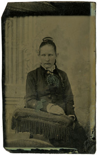 Tintype of unidentified, seated young woman, possibly blind, in a formal studio portrait