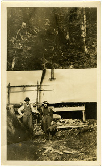 Two men stand outside canvas structure