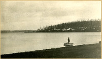 Man stands in rowboat at shoreline of Bellingham Bay with land and buildings in distance