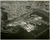 Aerial view of industrial waterfront, Bellingham, WA, showing landfill-based warehouses, marina, and breakwater, with residential neighborhoods inland
