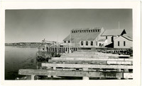 Warehouses on pier with beams of unfinished dock in foreground