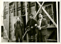 Three unidentified men, one holding a camera, stand in front of open door of warehouse