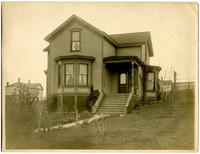 Front exterior of two-story house with front bay window and small porch