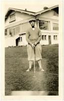 Man in golf attire posing with golf club