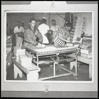 Six unidentified men wearing coveralls, and one a checkered workshirt, in a room with stacks of empty boxes.