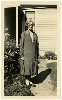 Woman in long overcoat stands in garden of residence
