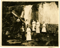 Six women, a man, and child pose on rocks below Whatcom Falls