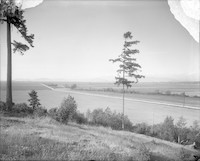Rural view from low hillside with roadway leading off into the distance.