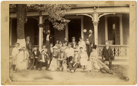 Large multigenerational group of people pose on steps and porch of house, with a penny-farthing high wheel bicycle leaning against tree on left