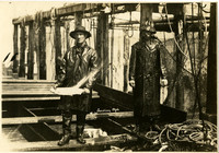 Two men in raingear stand on barge next to fishtraps