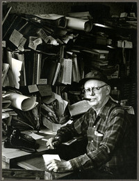 Man with cigar sits at desk with shelves cluttered with papers, binders, maps towering over him