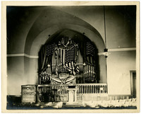 Large pipe organ in alcove draped with American flag