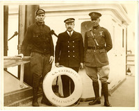 Three men pose with life float of S.S. Catherine D on deck of ship