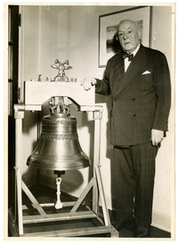 An elderly Archibald Shiels in suit and tie stands next to large bell on display
