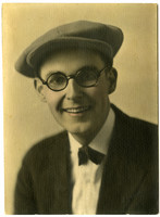 Studio portrait of smiling man in spectacles and wool cap