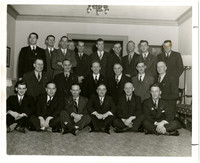 A group of men in suits pose in three rows in parlor or lobby