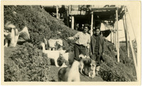 Two native Alaskans stand on hillside with several dogs on King Island with base of stilt house in background