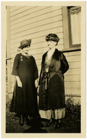 Two finely dressed women pose beside house