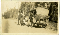 Vanse R. Bartlett and Mr. Dobbs , Chucknut Drive - two men repair tire on side of road