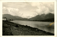 Postcard of rocky beach along Wrangell Narrows, southeast Alaska, with cluster of buildings in distance, forest and mountains beyond the water