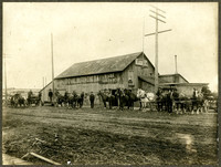 Several men with pairs of horses and mules, some attached to  buckboards or carriages waiting by the railroad tracks for train passengers to arrive and disembark at Port of Bellingham Livery Transport Co.