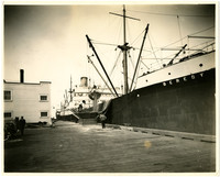 """A large cargo ship, """"Bereby,"""" at dock unloading grain or some other dry cargo."""
