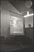 The screen on which one of Galen Biery's magic lantern slides is projected.
