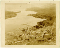 Aerial view of massive waterfront lumber mill with a number of log floats on water