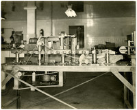 Horizontal mechanical boner machine, with visible cogs, gears, and pulleys, in a fish processing facility