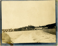Groundlevel view of water lapping on shore with cannery and small community in distance