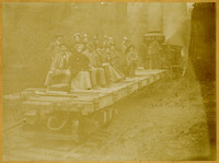 Approximately a dozen men and women in fine clothing, incliding J.H. Bloedel, gathered on a flatbed railcar, with a steam donkey and workmen on tracks behind