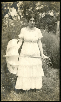 Young woman in long, frilly dress stands in garden holding parasol