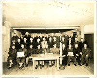 35 men in business attire and military uniforms pose in three rows behind table and American flag