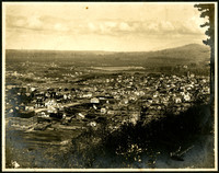 View from Sehome Hill of Bellingham neighborhoods, with the Whatcom County Agricultural Association Fair Grounds and Race Course in upper center, and forested foothills in distance