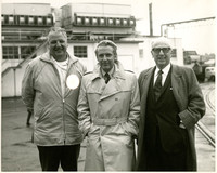 Three men in coats, standing in industrial yard, smile for camera