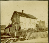 Exterior of simple two-story home swathed in striped bunting with part of baby carriage seen on right, in front of picket fence