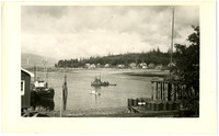 Small bay with village on opposite shore and several fishing tenders in water