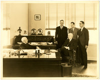Everett B. Deming, President of Pacific American Fisheries, and Arthur Deming, General Manager, sit behind large desk in office, with three men standing behind them