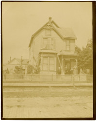 Front exterior of two-story Queen Anne-style residence with picket fence