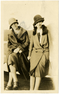 Two seated women wearing cloche hats and long coats