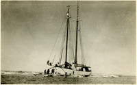 Several men tend to two-masted schooner where it has run aground