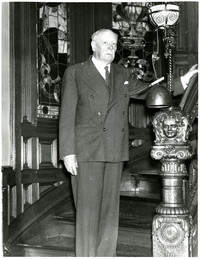 Roland Gamwell standing at bottom of ornate staircase in his house