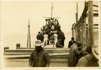 Workers on barges tend to fishtraps in foreground while passengers perch on crowded ferry to watch in background